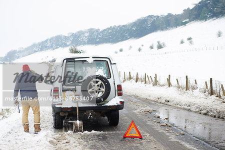Man working on broken down car in snow Stock Photo - Premium Royalty-Free, Image code: 6113-06753407