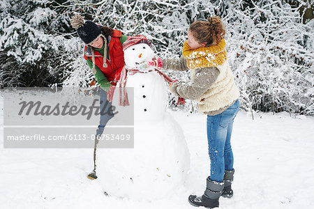 Mother and daughter making snowman Stock Photo - Premium Royalty-Free, Image code: 6113-06753409