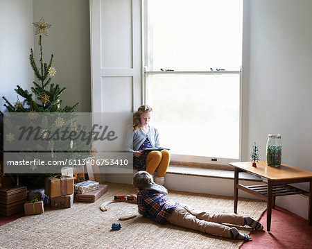 Children relaxing by Christmas tree Stock Photo - Premium Royalty-Free, Image code: 6113-06753410