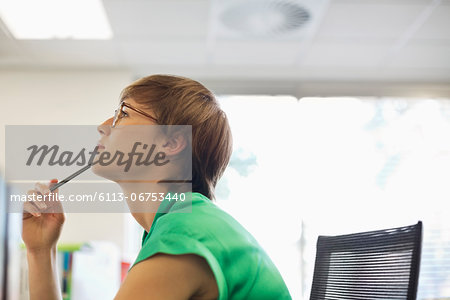 Businesswoman thinking at desk Stock Photo - Premium Royalty-Free, Image code: 6113-06753440
