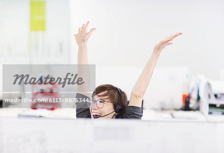 Businesswoman in headset cheering at desk Stock Photo - Premium Royalty-Free, Image code: 6113-06753443