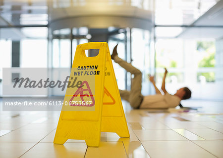 Businessman slipping on wet office floor Stock Photo - Premium Royalty-Free, Image code: 6113-06753567