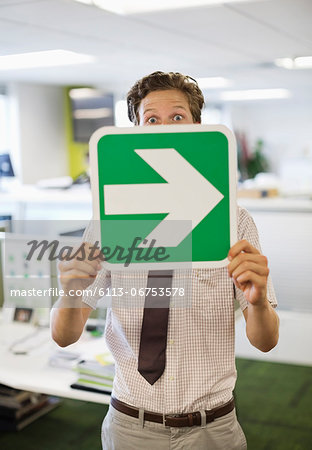 Businessman holding arrow sign in office Stock Photo - Premium Royalty-Free, Image code: 6113-06753578