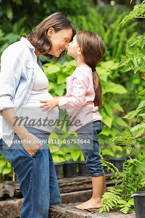Girl kissing pregnant mother outdoors Stock Photo - Premium Royalty-Free, Image code: 6113-06753644
