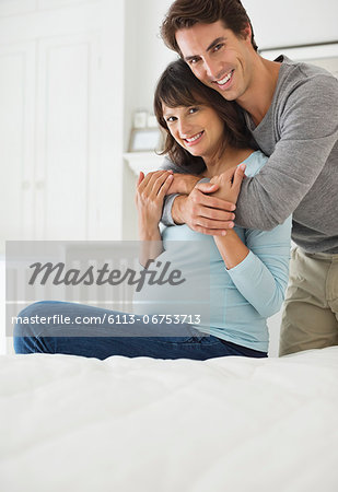 Man hugging pregnant girlfriend on bed Stock Photo - Premium Royalty-Free, Image code: 6113-06753713