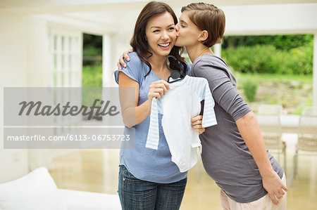 Woman giving pregnant friend baby clothes Stock Photo - Premium Royalty-Free, Image code: 6113-06753723