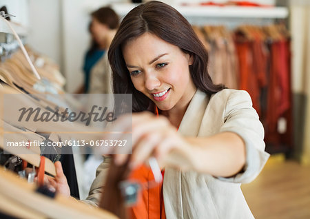 Woman shopping in clothes store Stock Photo - Premium Royalty-Free, Image code: 6113-06753727
