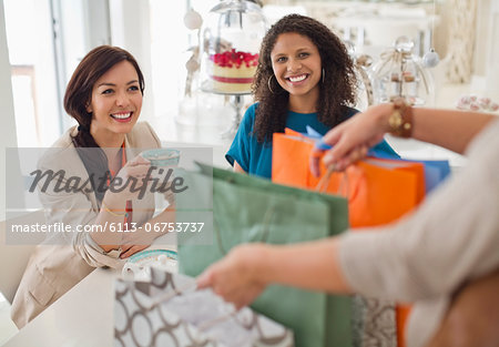 Woman showing friends shopping bags Stock Photo - Premium Royalty-Free, Image code: 6113-06753737