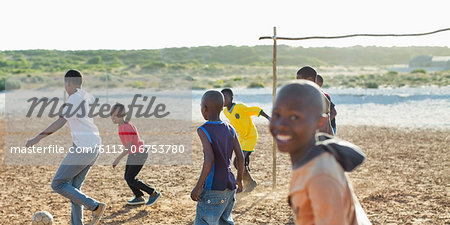 Boys playing soccer together in dirt field Stock Photo - Premium Royalty-Free, Image code: 6113-06753780