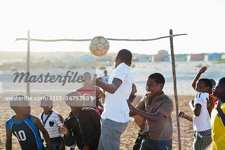 Boys playing soccer together in dirt field