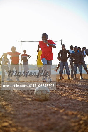 Boys playing soccer together in dirt field Stock Photo - Premium Royalty-Free, Image code: 6113-06753825