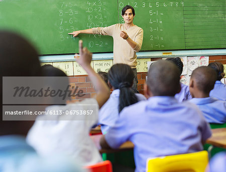 Teacher talking to students at chalkboard Stock Photo - Premium Royalty-Free, Image code: 6113-06753857