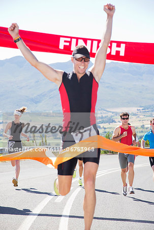 Runner crossing race finish line Stock Photo - Premium Royalty-Free, Image code: 6113-06753968