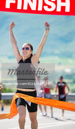 Runner crossing race finish line Stock Photo - Premium Royalty-Free, Image code: 6113-06753977