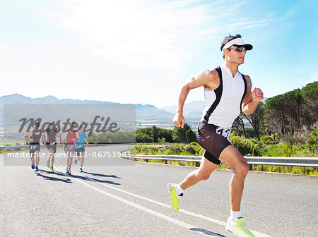 Runners in race on rural road Stock Photo - Premium Royalty-Free, Image code: 6113-06753983