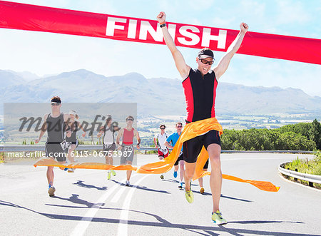 Runner crossing race finish line Stock Photo - Premium Royalty-Free, Image code: 6113-06753987