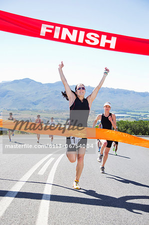 Runner crossing race finish line Stock Photo - Premium Royalty-Free, Image code: 6113-06754004