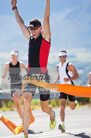 Runner crossing race finish line Stock Photo - Premium Royalty-Free, Image code: 6113-06754060