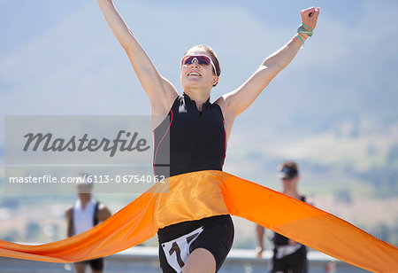Runner crossing race finish line Stock Photo - Premium Royalty-Free, Image code: 6113-06754062