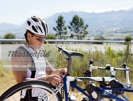Man adjusting bicycle outdoors Stock Photo - Premium Royalty-Free, Image code: 6113-06754077