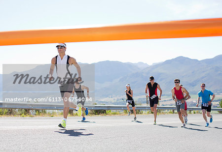 Runners crossing race finish line Stock Photo - Premium Royalty-Free, Image code: 6113-06754084