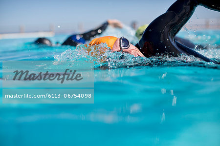 Triathletes in wetsuit splashing in pool Stock Photo - Premium Royalty-Free, Image code: 6113-06754098