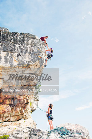 Climbers scaling steep rock face Stock Photo - Premium Royalty-Free, Image code: 6113-06754105