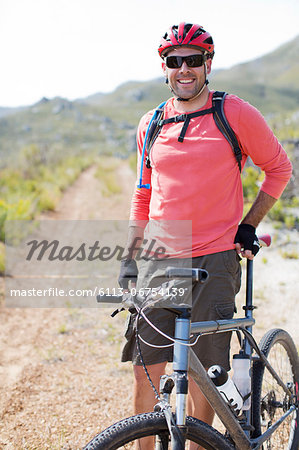 mountain biker smiling on dirt path Stock Photo - Premium Royalty-Free, Image code: 6113-06754139