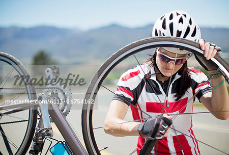 Cyclist adjusting tire on rural road Stock Photo - Premium Royalty-Free, Image code: 6113-06754162