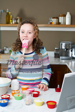 Girl licking spatula and baking Stock Photo - Premium Royalty-Free, Image code: 6113-06754191