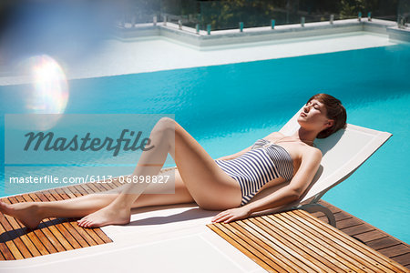 Woman sunbathing on lounge chair at luxury poolside Stock Photo - Premium Royalty-Free, Image code: 6113-06898827