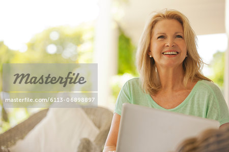 Smiling woman using laptop on patio Stock Photo - Premium Royalty-Free, Image code: 6113-06898897