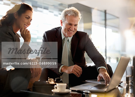 Smiling businessman and businesswoman using laptop in lobby Stock Photo - Premium Royalty-Free, Image code: 6113-06899059