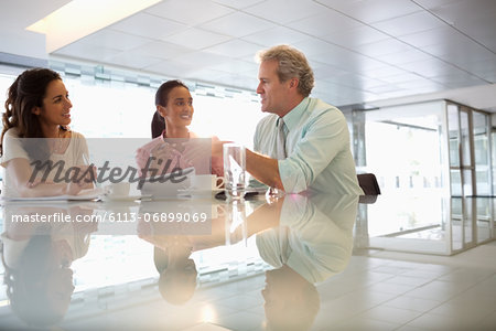 Business people talking in lobby Stock Photo - Premium Royalty-Free, Image code: 6113-06899069