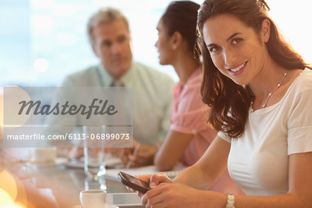 Portrait of smiling businesswoman with cell phone in meeting Stock Photo - Premium Royalty-Free, Image code: 6113-06899073