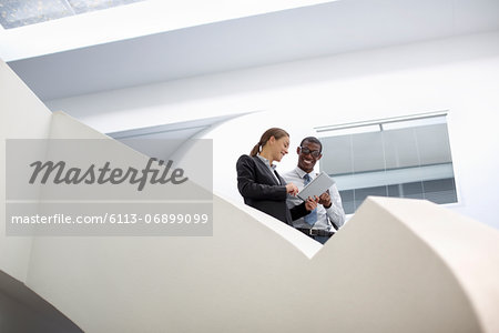 Businessman and businesswoman using digital tablet on modern staircase Stock Photo - Premium Royalty-Free, Image code: 6113-06899099