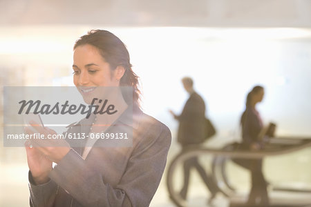 Smiling businesswoman text messaging with cell phone Stock Photo - Premium Royalty-Free, Image code: 6113-06899131