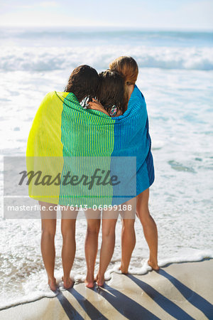 Friends wrapped in towel on beach Stock Photo - Premium Royalty-Free, Image code: 6113-06899188