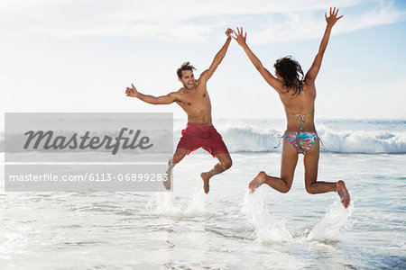 Couple jumping with arms raised on beach Stock Photo - Premium Royalty-Free, Image code: 6113-06899283