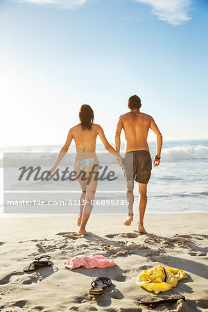 Couple holding hands and walking toward ocean on beach Stock Photo - Premium Royalty-Free, Image code: 6113-06899285