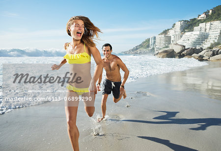 Man chasing happy woman on beach Stock Photo - Premium Royalty-Free, Image code: 6113-06899290