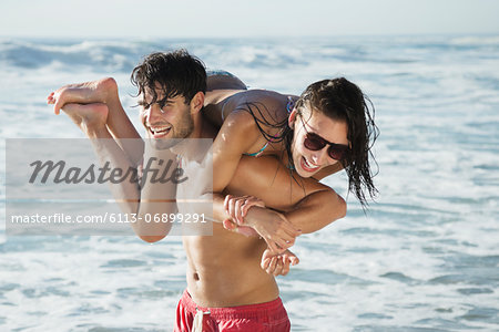 Happy man carrying woman on beach Stock Photo - Premium Royalty-Free, Image code: 6113-06899291