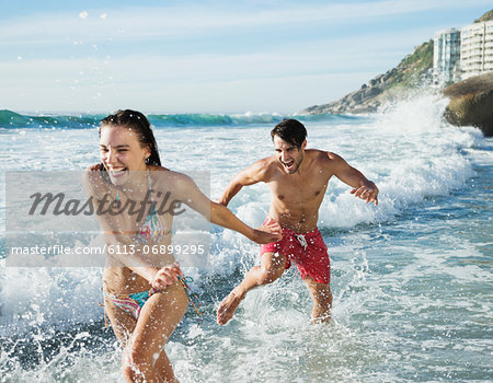 Playful couple splashing in ocean surf Stock Photo - Premium Royalty-Free, Image code: 6113-06899295