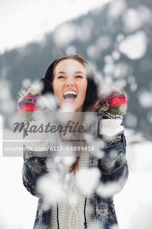 Enthusiastic woman enjoying falling snow Stock Photo - Premium Royalty-Free, Image code: 6113-06899414