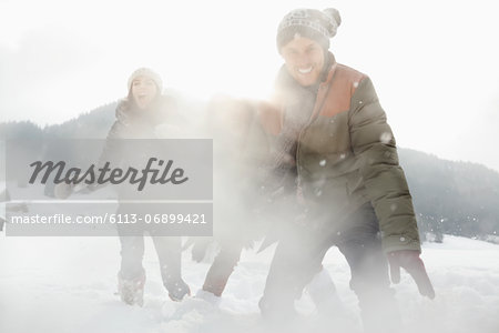 Portrait of playful friends enjoying snowball fight in field Stock Photo - Premium Royalty-Free, Image code: 6113-06899421