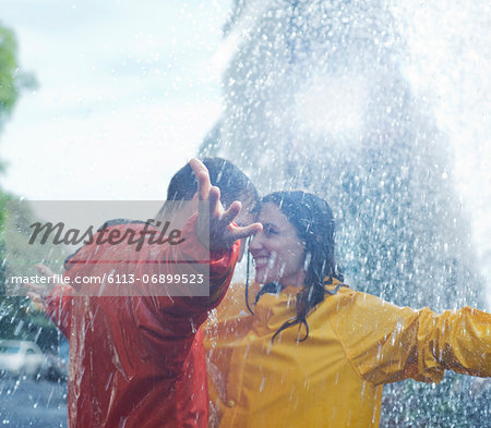 Happy couple dancing in rain Stock Photo - Premium Royalty-Free, Image code: 6113-06899523