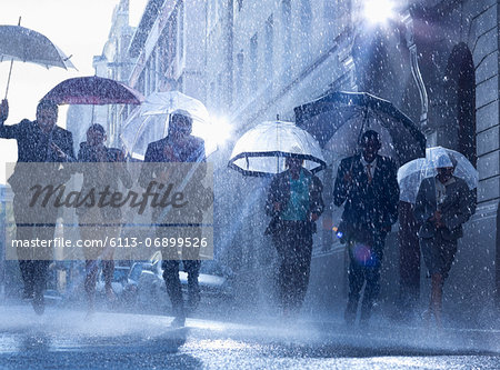 Business people with umbrellas running in rain Stock Photo - Premium Royalty-Free, Image code: 6113-06899526