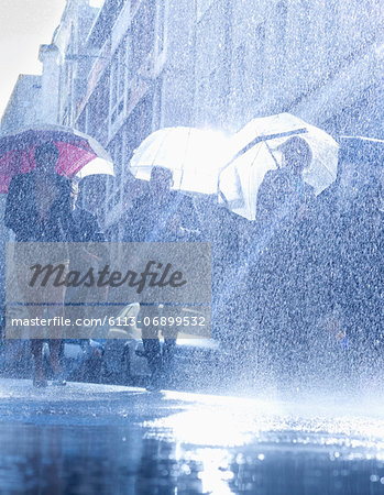 Business people with umbrellas in rain Stock Photo - Premium Royalty-Free, Image code: 6113-06899532