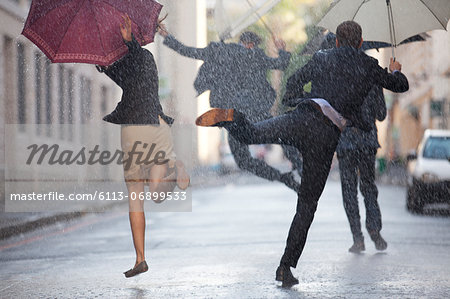 Business people with umbrellas dancing in rain Stock Photo - Premium Royalty-Free, Image code: 6113-06899533