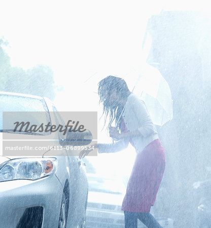 Woman with umbrella reaching for car door handle in rain Stock Photo - Premium Royalty-Free, Image code: 6113-06899534